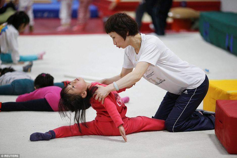Una niña es apoyada por su entrenadora durante la clase de gimnasia. (Foto: dailymail.co.uk)