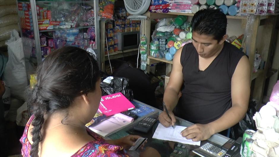 El encargado de la tienda apunta la cantidad de alimentos y adjunta el vale de compra. (Foto: Alejandro Balán/Soy502)