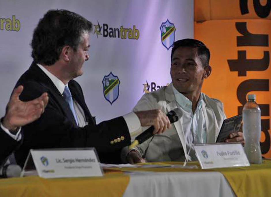 Pedro Portilla, presidente de Comunicaciones, sostiene el microfono mientras felicitan a Rigoberto Gómez, quien recibirá un homenaje ante los aficionados cremas
