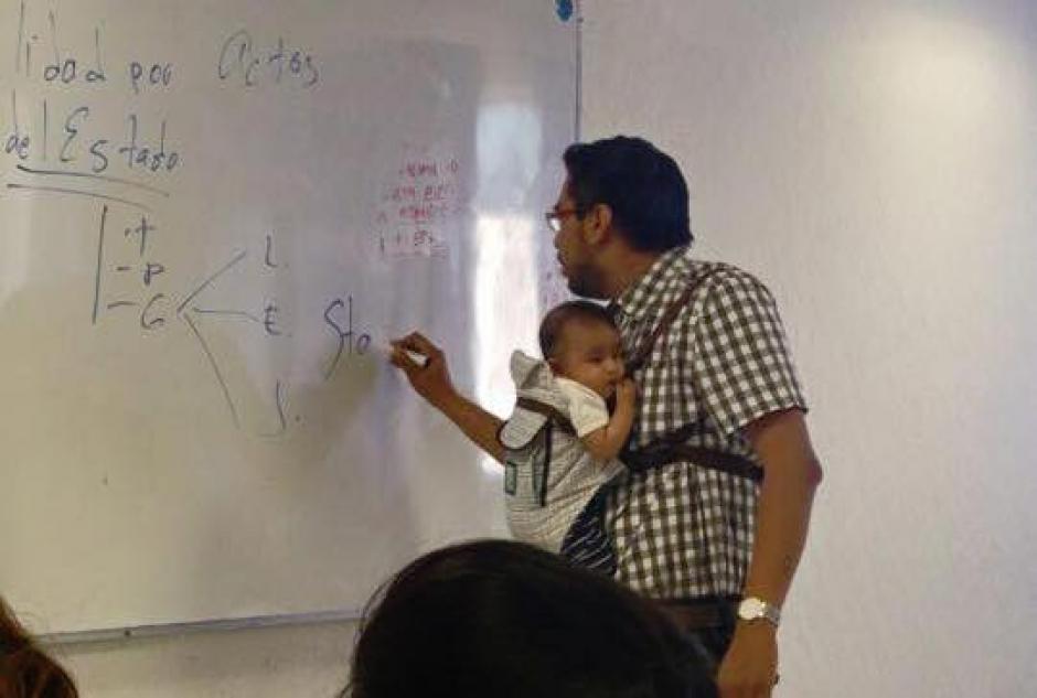 Maestro carga bebé de alumna en clase foto