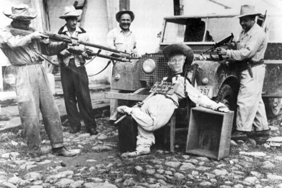 """Liberacionistas apuntan a un muñeco con rostro de Arbenz y el rótulo """"me yaman de Rusia"""" (sic). Chiquimula ,1954. (Foto: Twitter/@GuatHistorica)"""