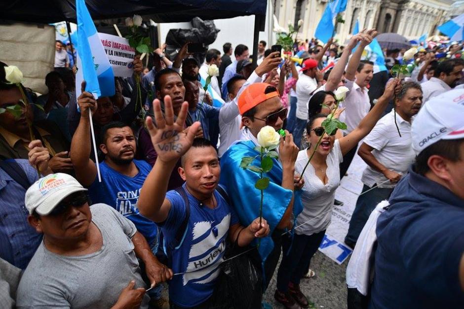 Convocados por el movimiento Justicia Ya varias personas con rosas blancas y agua pura lograron retirar a los que bloquearon los ingresos. (Foto: Wilder López/Soy502)