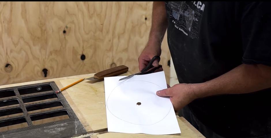 El hombre prepara una rueda para colocarla en lugar de la sierra de metal. (Captura de pantalla: John Heisz/YouTube)
