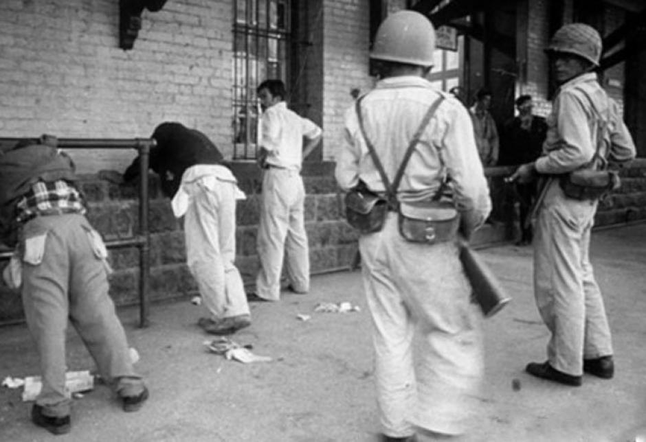 Soldados retienen y revisan a manifestantes. Ciudad Guatemala, julio 1960. (Foto: Twitter/@GuatHistorica)