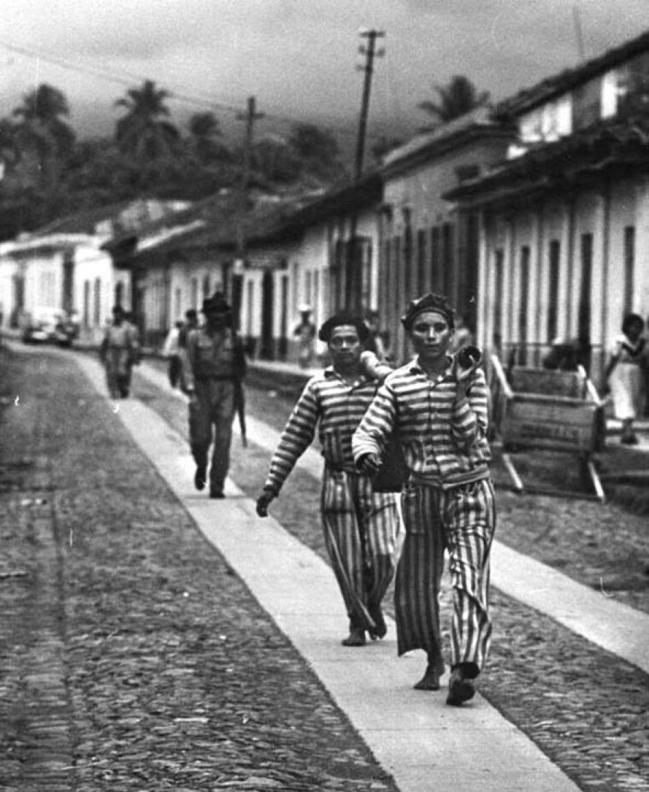 Dos presos acarrean cubetas con agua en un travesaño mientras un guardia los sigue. Escuintla 1953. (Foto: Twitter/@GuatHistorica)