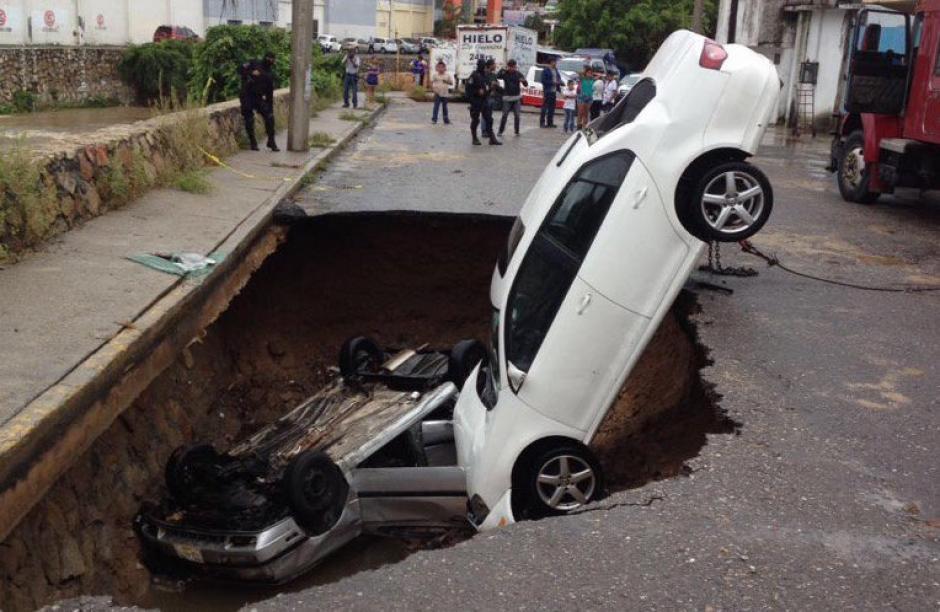 Los carros quedaron atrapados dentro de un hoyo en una calle de Acapulco debido a un socavón provocado por las lluvias. (Foto: Alejandro Villalvazo)