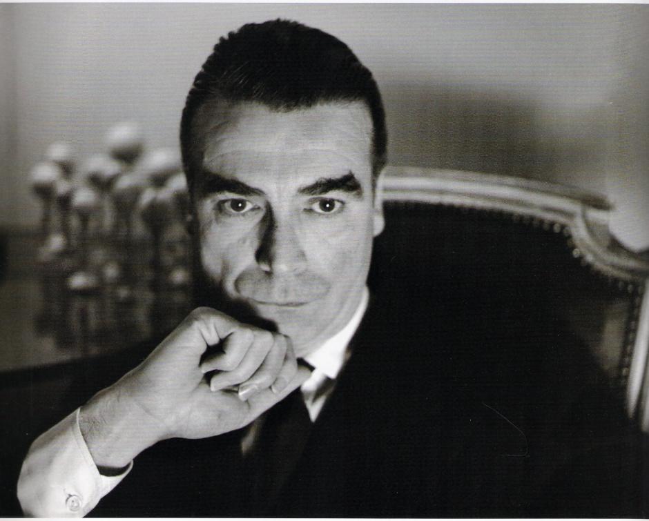 Fotografía del español Cristóbal Balenciaga con su mano en la barbilla.