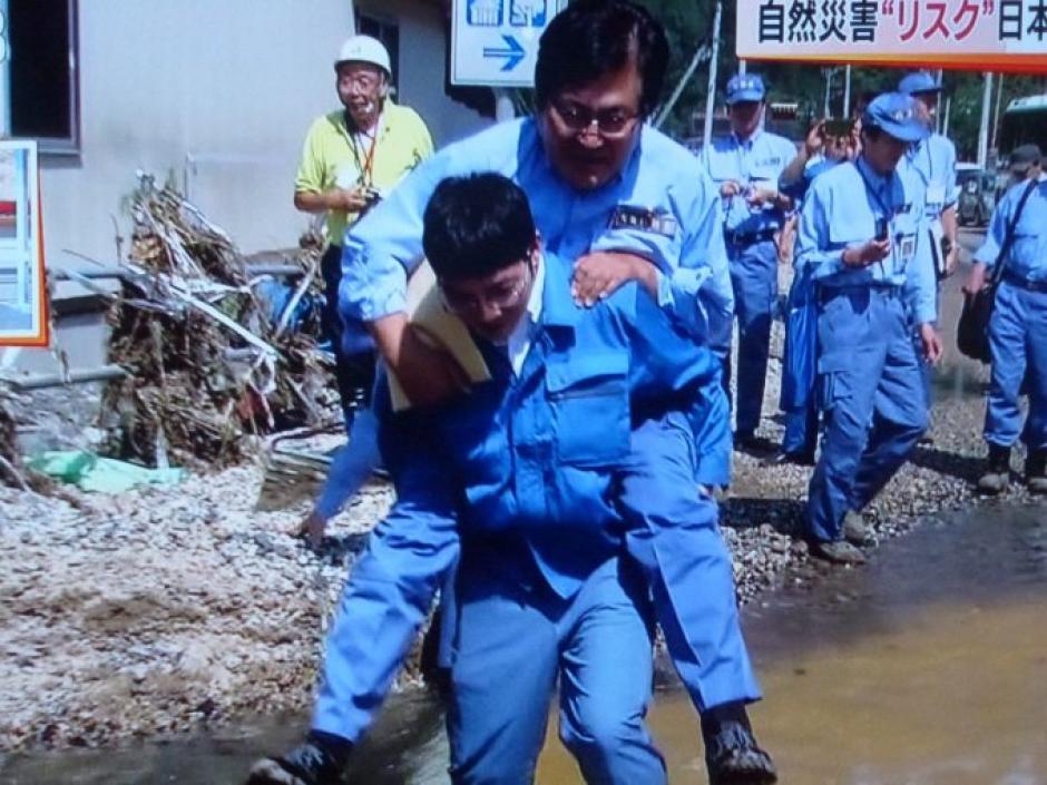 El funcionario no llevaba botas y pidió a un trabajador que lo ayudara a cruzar un charco. (Foto: Excélsior)