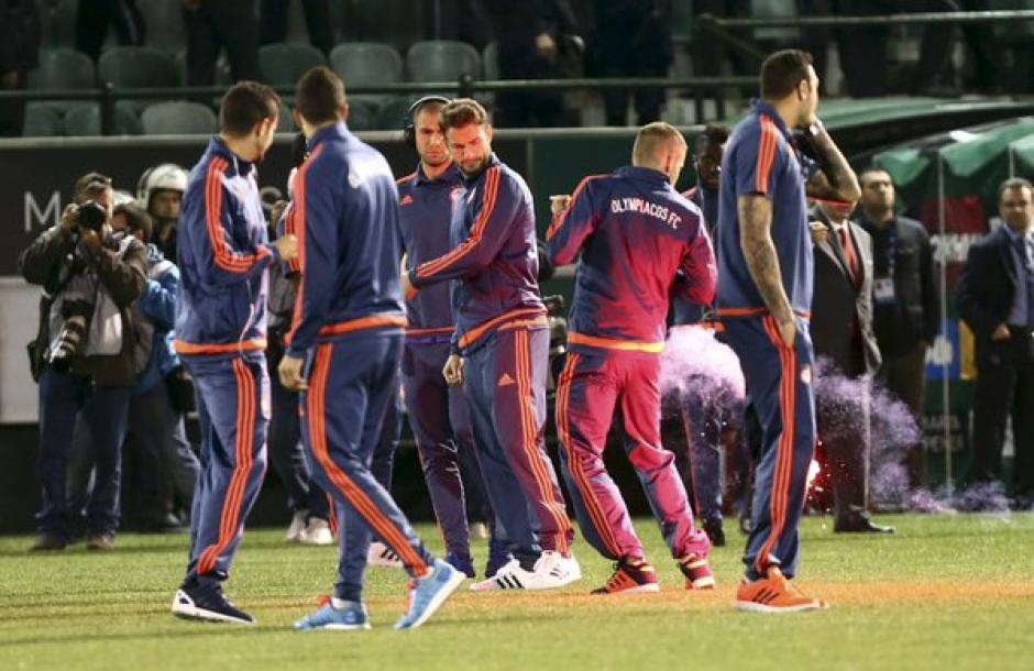 Cientos de bengalas cayeron a la cancha cuando el Olympiacos salió a calentar.