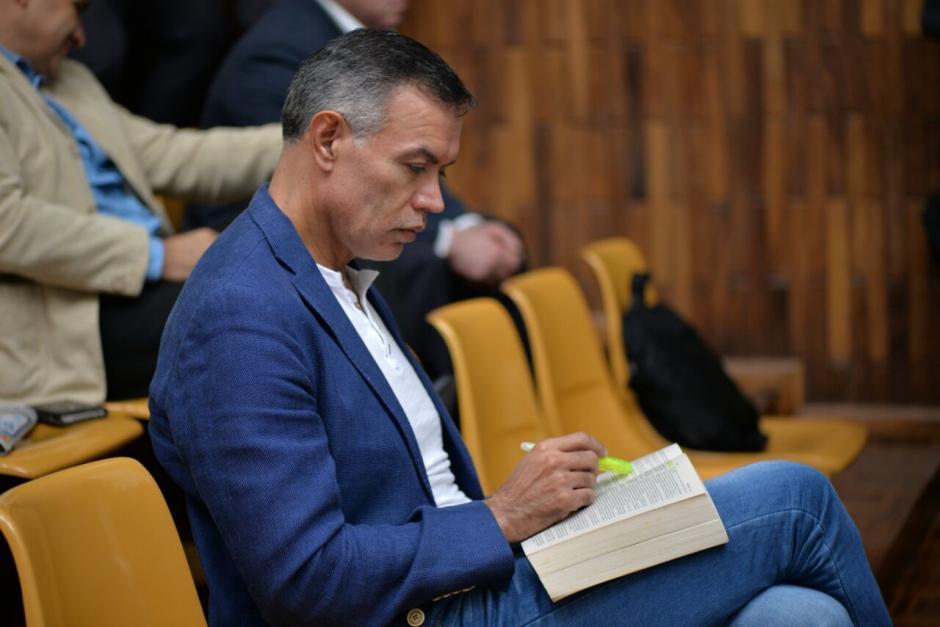 Juan de Dios Rodríguez lee la Biblia, mientras su abogado presenta la defensa técnica. (Foto: Wilder López/Soy502)