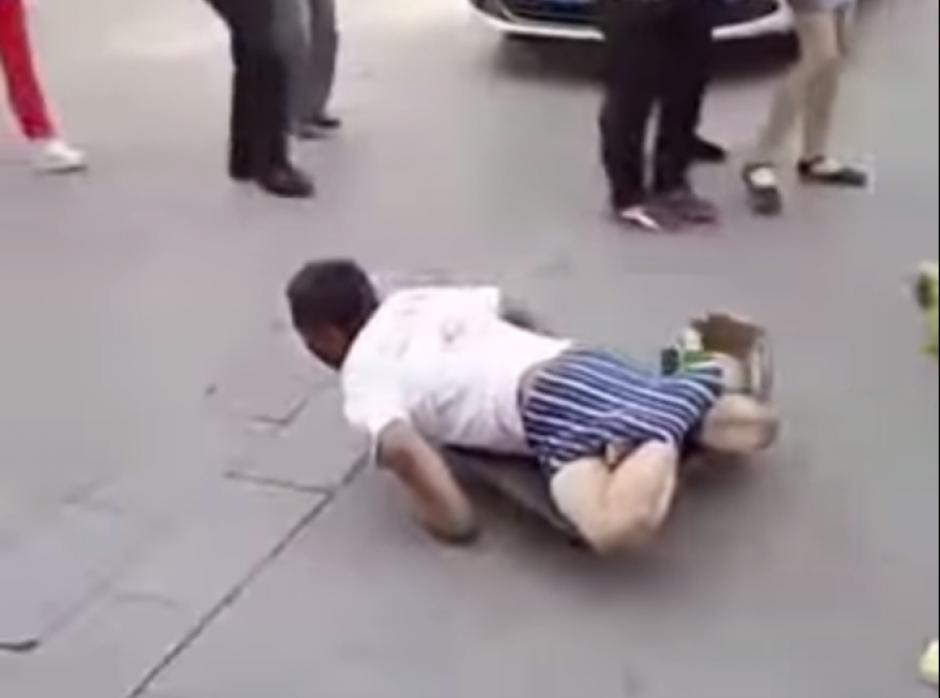 El hombre tiene sujetadas las piernas para aparentar que es discapacitado. (Captura de pantalla: Iwe Al/YouTube)