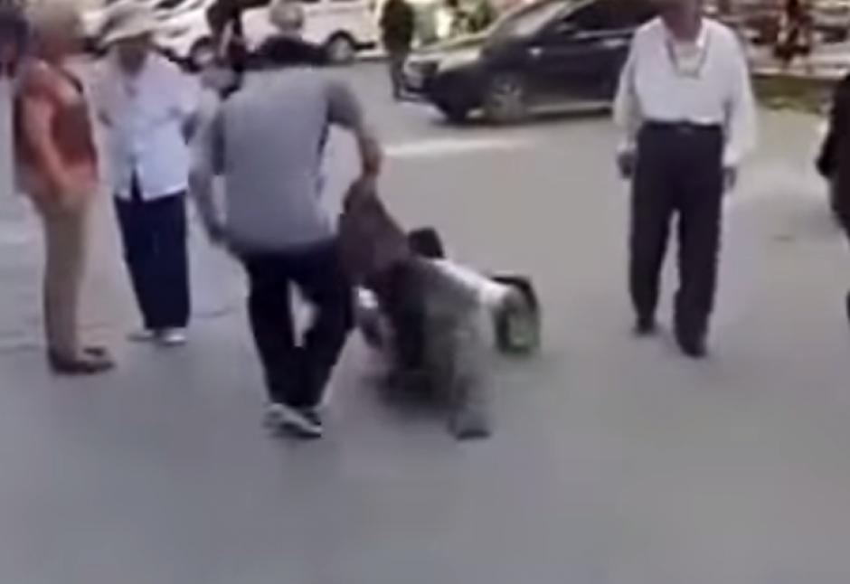 El chico trata de quitarle el pantalón ante la mirada de todos. (Captura de pantalla: Iwe Al/YouTube)