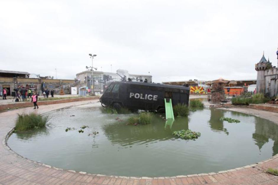 Los visitantes que acceden al recinto se encuentran con un castillo a medio derruir, furgones de policía, barcas cargadas de refugiados y ferias en las que no se puede obtener premio alguno.