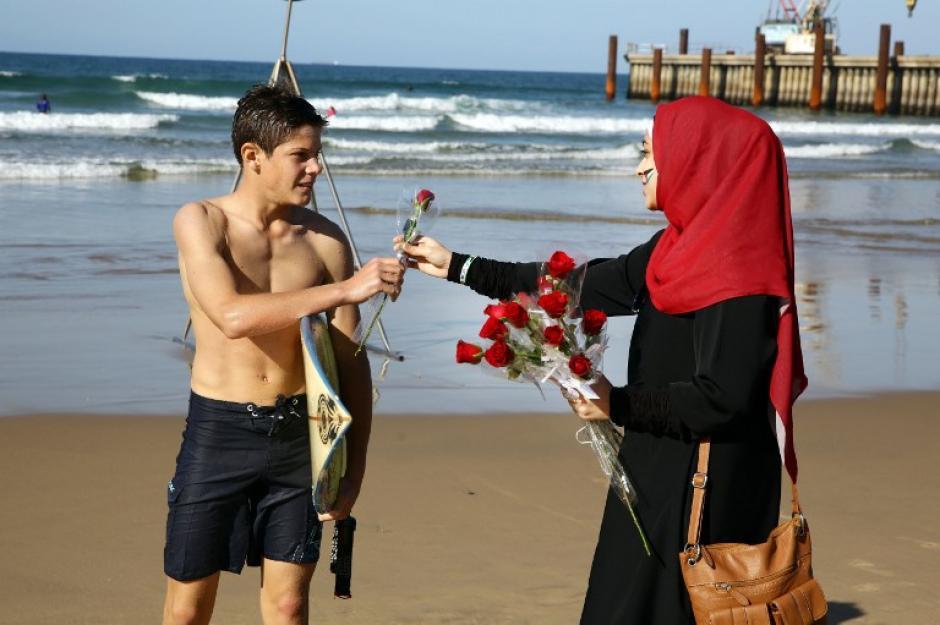 """Una voluntaria da una rosa a una persona que practica surf, como parte de los """"pétalos para Palestina"""" Proyecto Paz a los miembros del público a la playa norte en Durban. Esto busca crear una conciencia de el conflicto en Oriente Medio y la situación de las rosas Palestinians. Unas mil fueron distribuidos por un grupo de voluntarios en la playa. """"las rosas son vistas como un gesto simbólico de difundir el mensaje de amor, paz y unidad"""", dijo un voluntario. (Foto: AFP/ Rajesh JANTILAL)"""