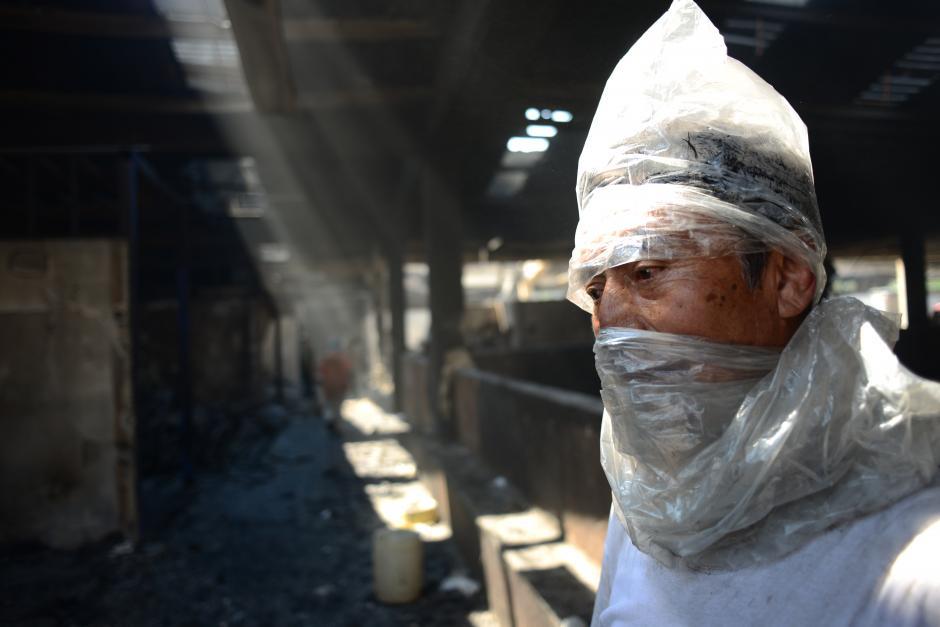 Como pudieron, los inquilinos de la Terminal de la Zona 4, se protegen de la ceniza y los restos de humo luego del incendio que redujo a cenizas sus negocios. (Foto: Jesus Alfonso/Soy502)