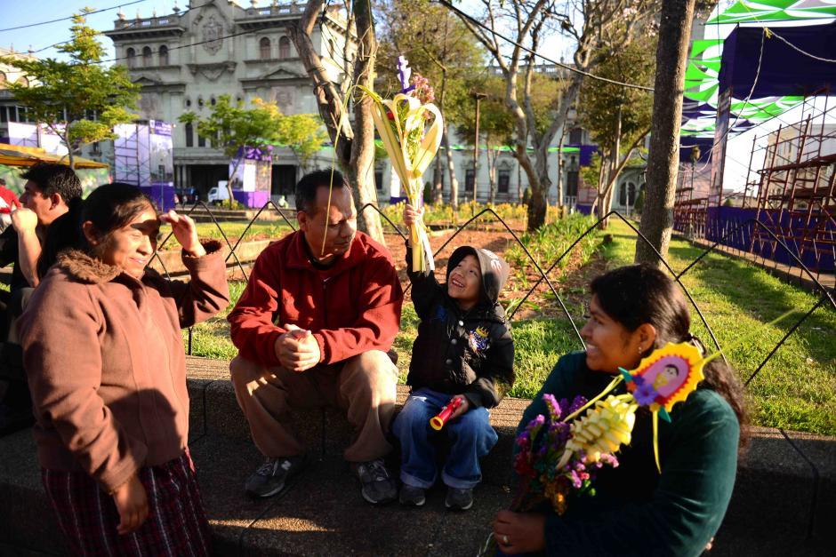 Las familia Cañizales llegó al parque central antes de las 7 de la mañana para asistir a la misa. El más pequeño se mostraba entusiasmado con el ramo que sus padres adquirieron. (Foto: Jesús Alfonso/Soy502)