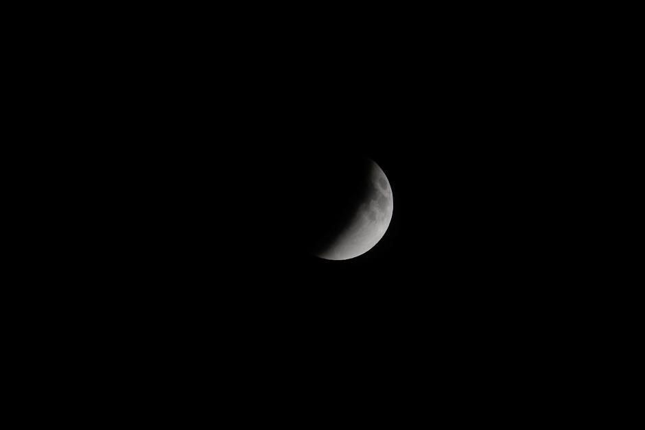 La cara de la Luna ya está casi escondida. Los guatemaltecos se preguntan con ansías si podrán ver el resplandor rojizo después. (Foto: Jesús Alfonso/Soy 502).