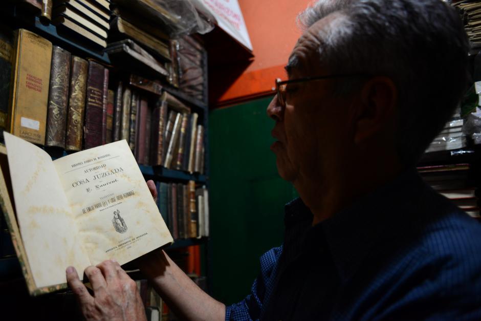 """Julio Gálvez, propiertario de la librería """"El Búho"""", muestra una copia de un libro de 1888; una verdadera reliquia entre su colección. (Foto: Jesús Alfonso/Soy502)"""
