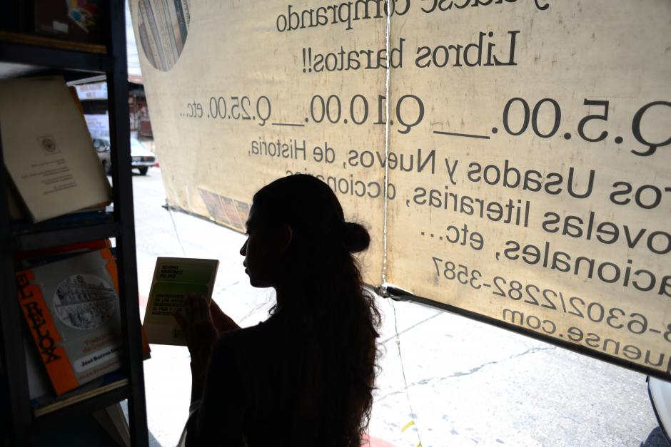 """Una jóven mujer busca libros entre las ofertas. """"Los verdaderos lectores son los que compran libros"""", señaló Julio Gálvez, propietario de la Librería """"El Búho""""."""