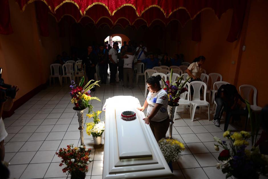 La hermana de Kevin Díaz ora junto al féretro, durante el velatorio en la iglesia evangélica Luz y Vida de San Miguel Petapa, previo a que el equipo Crema llegara para ofrecer el pésame a la familia. (Foto: Jesús Alfonso/Soy502)