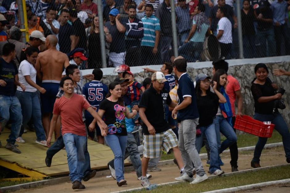 Los aficionados que no participaron en los enfrentamientos entre seguidores de la Usac y Comunicaciones, debieron ser evacuados por la gramilla del estadio Revolución. (Foto: Nuestro Diario)