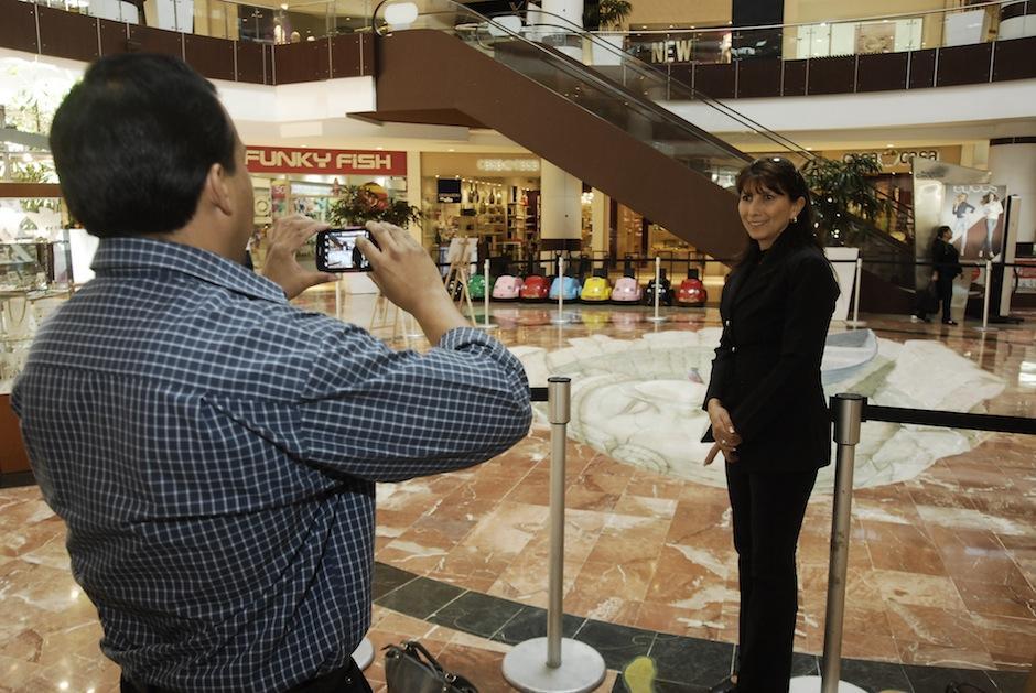 Los visitantes del centro comercial posan entusiasmados junto a la pieza 3D, que aún no ha sido terminada. (Foto: Jesús Alfonso/Soy502)