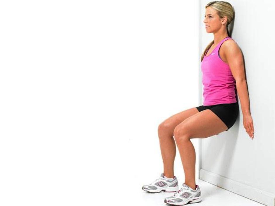 Con la espalda apoyada en la pared y los pies apartados, baja lentamente el cuerpo doblando las piernas. (Foto:  trainer.es)