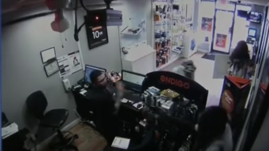 Uno de los individuos le apunta con un arma al encargado de la tienda. (Captura de pantalla: Dev Null/YouTube)