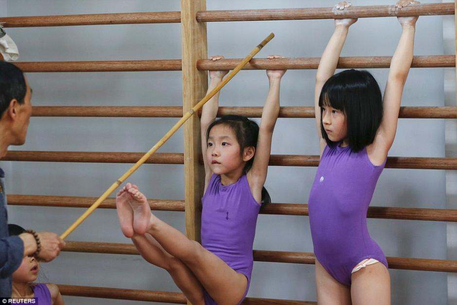 Una niña intenta estirar las piernas y llegar a un palo sostenido por su entrenador durante las clases de gimnasia. (Foto: dailymail.co.uk)