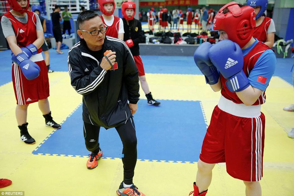 Mujeres estudiantes escuchan a su profesor en un gimnasio de boxeo en la escuela deportiva Shichahai en Beijing. (Foto: dailymail.co.uk)