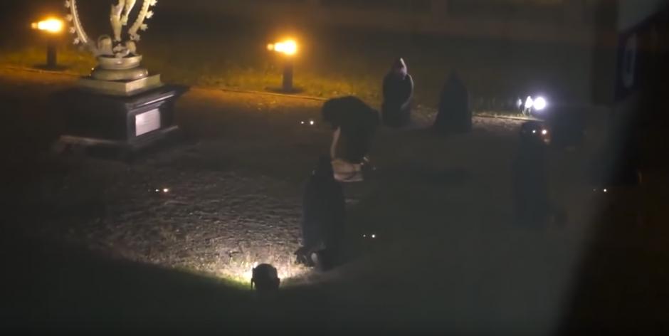 Una de las personas vestidas con túnica negra la empieza a apuñalar. (Captura de pantalla: Ron Johnson/YouTube)