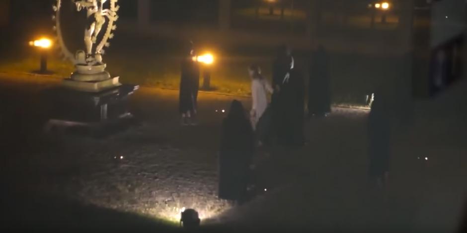 De pronto una de las personas se quita la túnica negra y se puede ver a una mujer con una túnica blanca. (Captura de pantalla: Ron Johnson/YouTube)