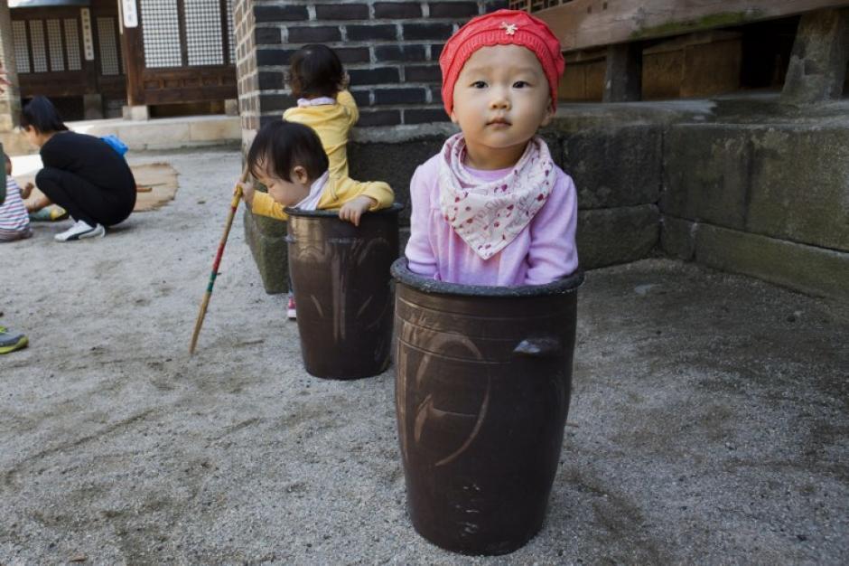 Una niña coreana se esconde en una ceramica en un juego tradicional