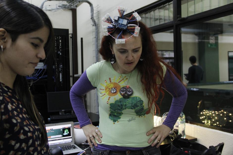 Tayana explica a una de las participantes sobre una chaqueta que emite sonido al contacto con la piel.(Foto: Fredy Hernández/Soy502)