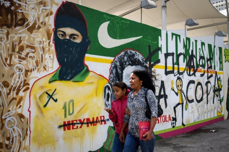 Las personas caminan frente un graffiti que representa al futbolista brasileño Neymar el que fue manchado con una capucha usada por miembros del grupo anarquista conocido como Bloque Negro que está en contra de la Copa Mundial de Brasil 2014 torneo de fútbol, en Río de Janeiro, Brasil. (Foto: AFP/ YASUYOSHI CHIBA