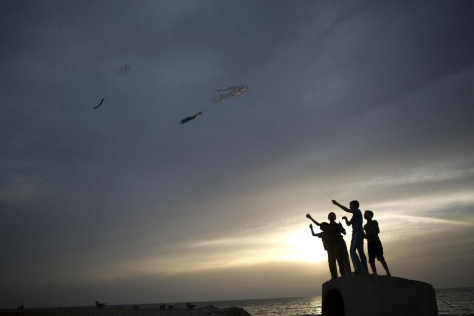 Jóvenes palestinos sostienen una cuerda conectada a una cometa el 29 de mayo de 2014 en la ciudad de Gaza. (Foto: AFP / MOHAMMED ABED)