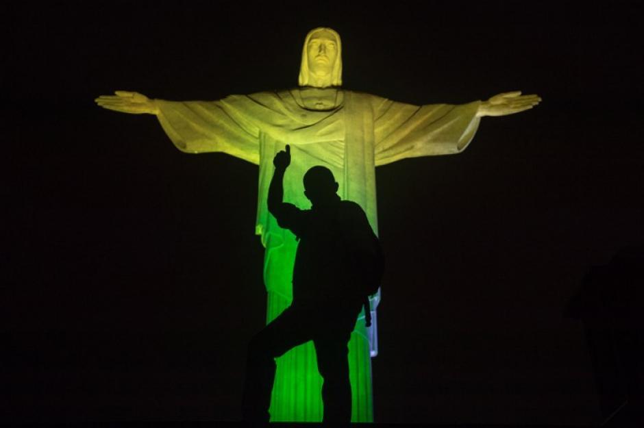La estatua del Cristo Redentor se ve iluminado con los colores de la bandera de Brasil, durante el cambio de colores de los 32 naciones que participan en la Copa Mundial de la FIFA Brasil 2014 en la cima del Corcovado colina en Río de Janeiro, Brasil, en la víspera del evento. (Foto: AFP / YASUYOSHI CHIBA)