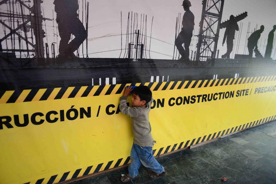 Un niño juega en la manta de un sitio en construcción mientras su madre vende dulces a los transeuntes en la zona 10 capitalina. (Foto: Jesús Alfonso/Soy502)