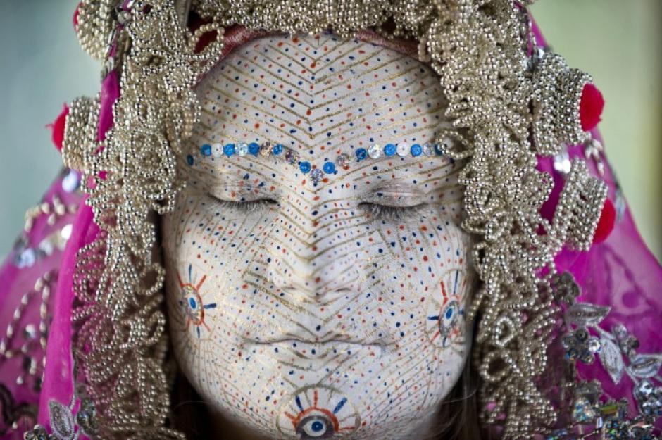 Arleta Sahiti una mujer Bosnia Kosovar muestra su cara después que fuera pintada por una mujer durante una presentación de la ceremonia de boda tradicional de las mujeres bosnias de la región Zhupa en el Museo Etnológico de Pristina. Como parte de la tradición, las ancianas preparan a jovenes, pintando sus rostros en muchas capas de colores. Los círculos de oro simbolizan los ciclos de la vida. (Foto: AFP / Armend Nimani)