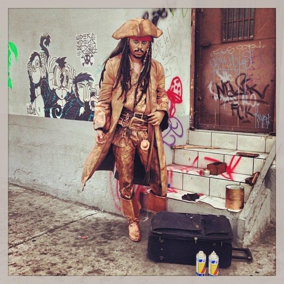 """Daniel es un artista callejero que se viste como """"Jack Sparrow""""el personaje de ficción de la serie cinematográfica """"Los Piratas del Caribe"""". Todos los días se instala con todos sus instrumentos de pintura sobre la 6a. avenida de la zona 1. En ese lugar entretiene con su arte a los transeúntes que pasan por el lugar. Foto Jesús Alfonso/Soy502"""