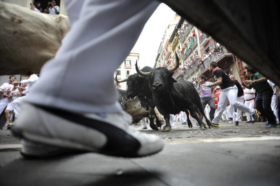 Los participantes corren delante de los toros de Torrestrella durante el primer día de las fiestas de San Fermín, el 7 de julio de 2014, en Pamplona, al norte de España. El festival es un símbolo de la cultura española que atrae a miles de turistas para ver las corridas de toros a pesar de las manifestaciónes en contra de la tradición por parte de grupos de derechos de los animales. (Foto: AFP/ANDER GILLENEA)