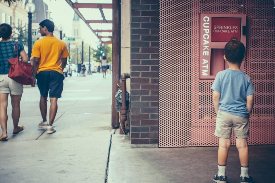 """En la """"ciudad que nunca duerme"""", la última ocurrencia de una pastelería de la Gran Manzana ha sido abrir un """"cajero automático"""" para que los neoyorquinos puedan saciar su apetito por los """"cupcakes"""" a cualquier hora del día.La empresa pastelera """"Sprinkles Cupcakes"""" ha instalado los dispensadores de estos """"cupcakes"""". Un niño observa la forma en que se presenta el ATM de los pastelillos.(Foto: EFE)"""