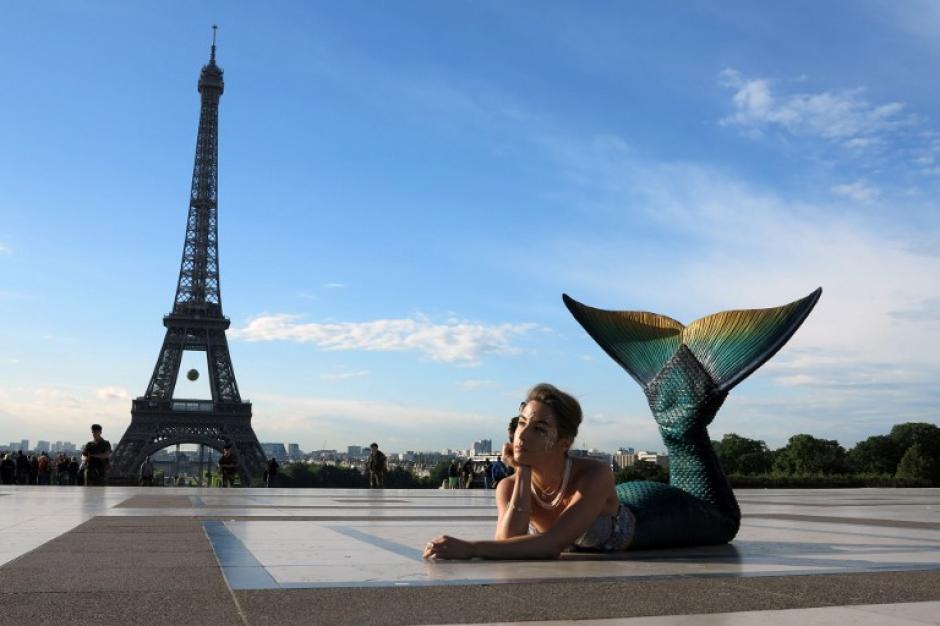 Una modelo vestida como una sirena posa delante de la Torre Eiffel en la salida del sol en París. (Foto: (AFP / LUDOVIC MARIN)