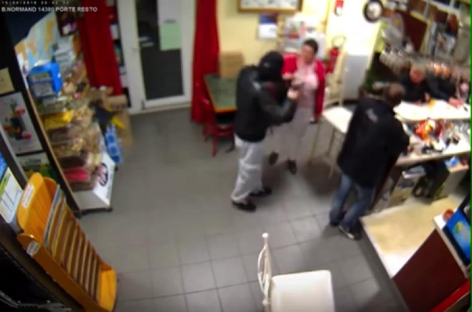 El asaltante apunta con la pistola a los compradores y la señora se dirige hacia él con el bebé. (Foto: YouTube)
