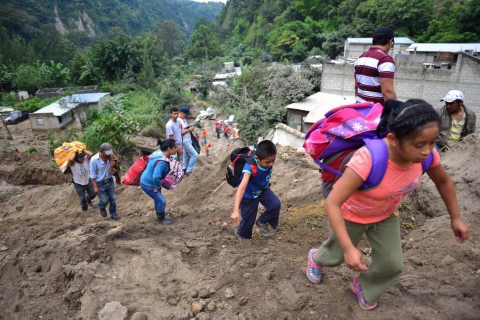Niños y familias completas se retiran del lugar del desastre en El Cambray II en Santa Catarina Pinula. (Foto: Jesús Alfonso/Soy502)