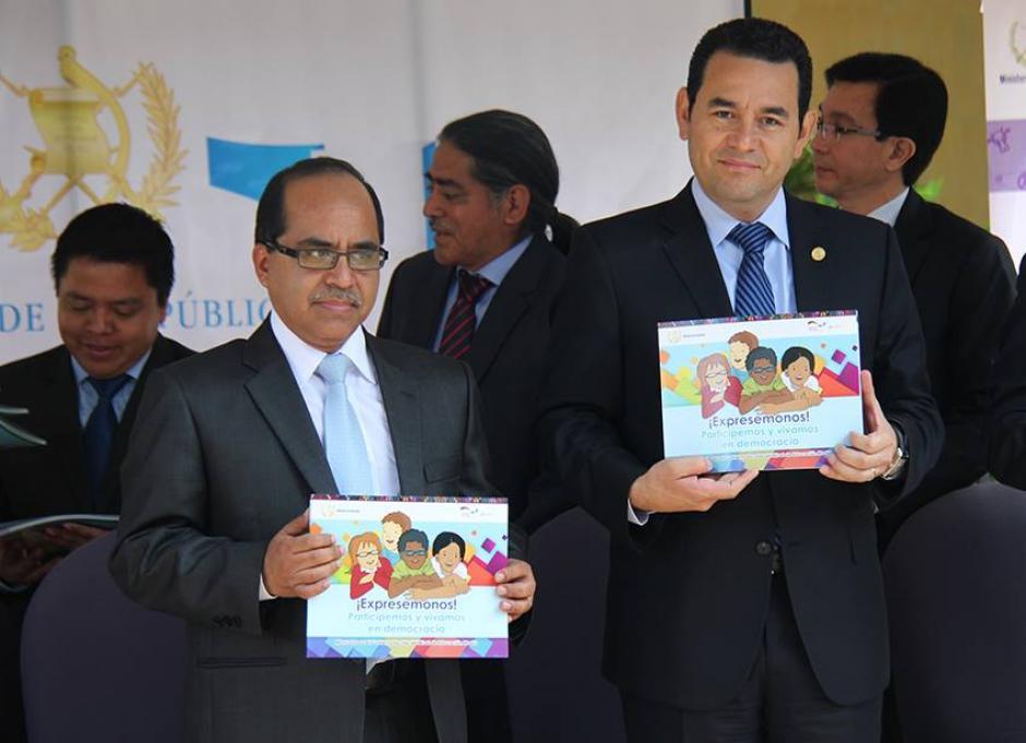 Ministro de Educación, Oscar López y el presidente, Jimmy Morales posan con el manual de gobierno escolar. (Foto: Mineduc)