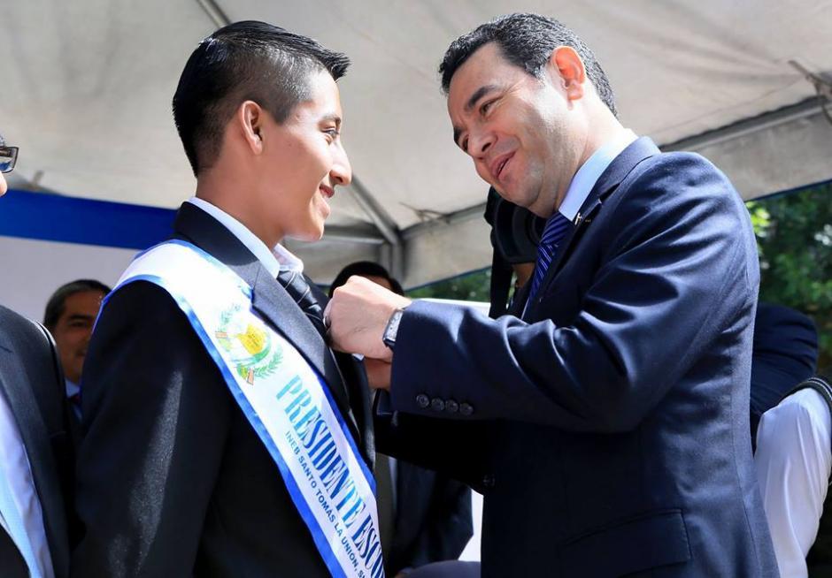 El presidente entregó un pin al presidente de una escuela en Alta Verapaz. (Foto: Presidencia)