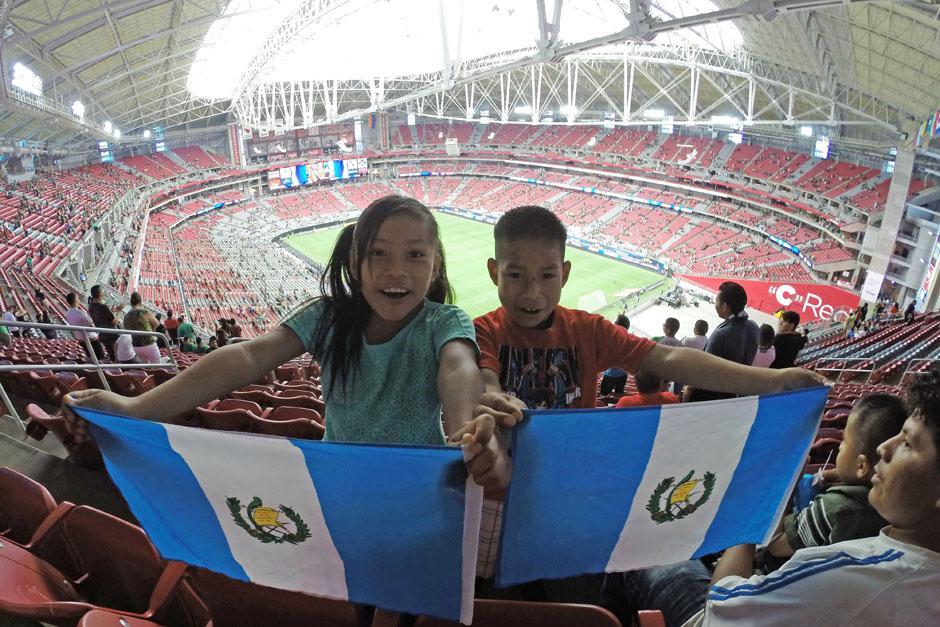 Niños guatemaltecos con la bandera dentro del estadio de la Universidad de Phoenix