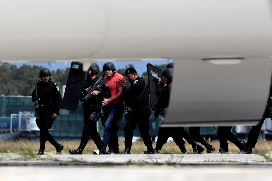 Con escudos y armas de grueso calibre, los elementos de la PNC llevaron a Orellana hasta la avioneta que lo traslada a Estados Unidos.(Foto: Esteban Biba/EFE)