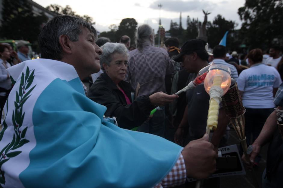 Solidaridad entre los asistentes a la hora de prender las antorchas.(Foto: Esteban Biba/EFE)